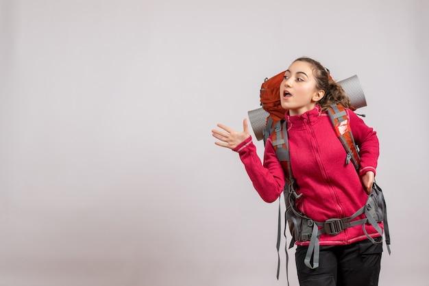 Ładna kobieta z dużym plecakiem stoi machając ręką na szaro