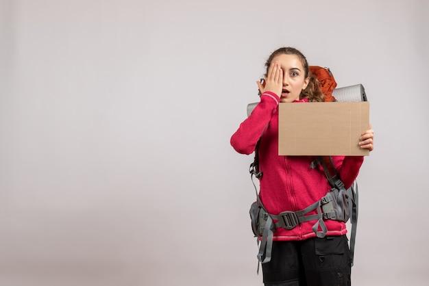 Ładna kobieta z dużym plecakiem trzymająca karton kładący rękę na oku
