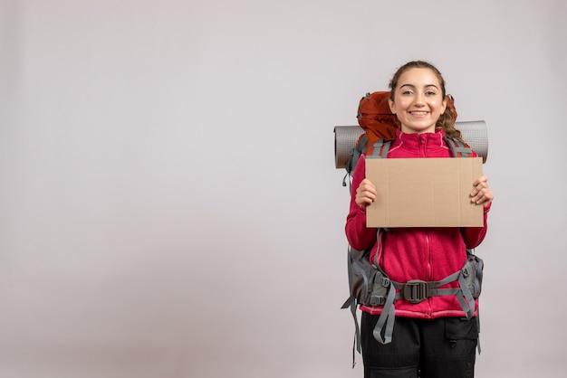 Ładna kobieta z dużym plecakiem trzymająca karton obiema rękami