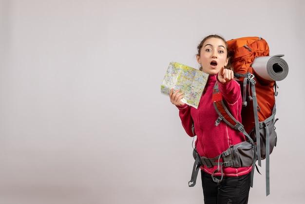 Ładna kobieta z dużym plecakiem trzymająca mapę wskazującą na aparat