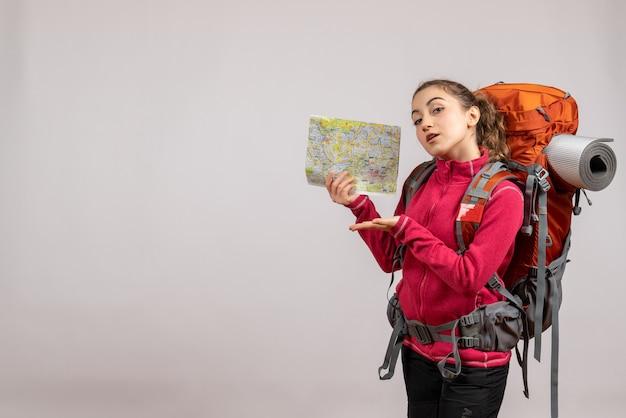 Ładna kobieta z dużym plecakiem trzymającym mapę