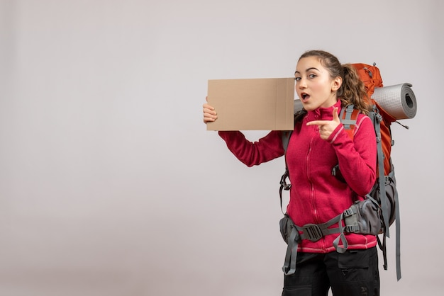 Ładna kobieta z dużym plecakiem wskazującym na karton