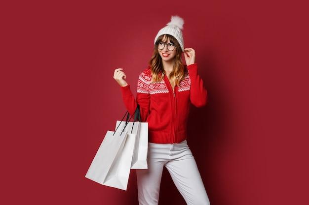 Ładna kobieta z falistymi włosami stoi z białymi torba na zakupy