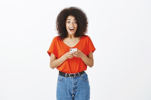 Ładna kobieta z fryzurą afro z jej smartfonem w studio