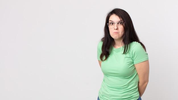Ładna kobieta z głupkowatym, szalonym, zdziwionym wyrazem twarzy, nadętymi policzkami, uczuciem wypchania, tłusta i pełna jedzenia