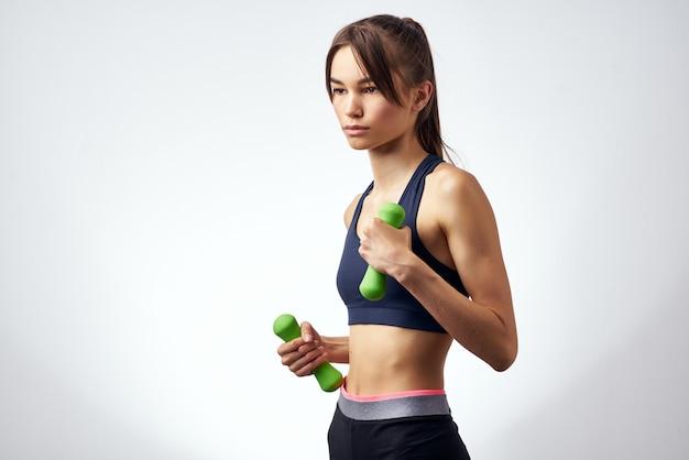 Ładna kobieta z hantlami w ręku z treningu ćwiczenia jasnym tle. zdjęcie wysokiej jakości