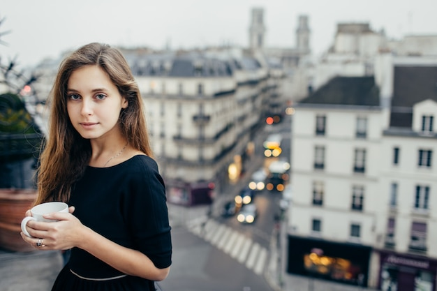 Ładna kobieta z kawą na balkonie