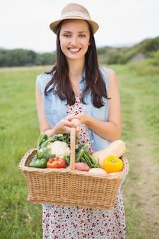 Ładna kobieta z koszem warzywa na słoneczny dzień