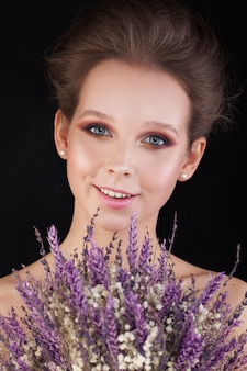 Ładna kobieta z kwiatami na czarnym tle. piękno portret