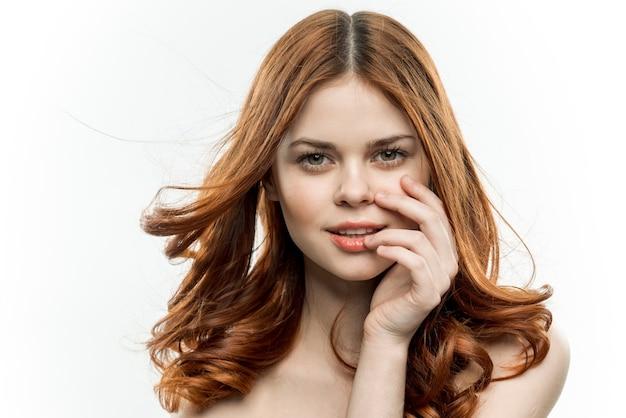 Ładna kobieta z luźnymi rudymi włosami i nagimi ramionami