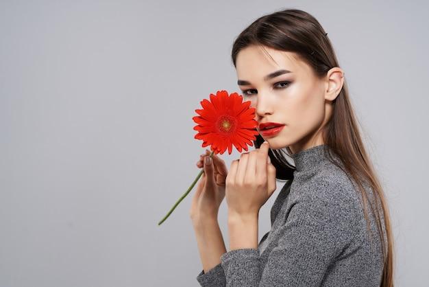 Ładna kobieta z modelem kosmetyków na prezent z czerwonego kwiatu