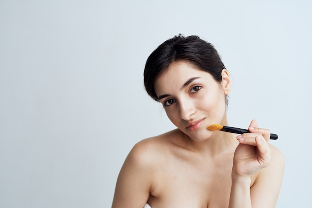 Ładna kobieta z nagimi ramionami, stosując makijaż na styl życia twarzy. wysokiej jakości zdjęcie