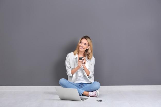 Ładna kobieta z nowoczesnym laptopem siedzi w pobliżu szarej ściany
