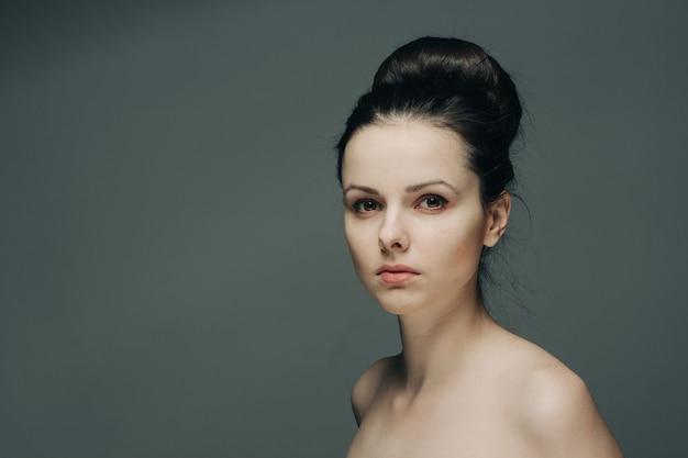 Ładna kobieta z odkrytymi ramionami na modelu szarej fryzury.