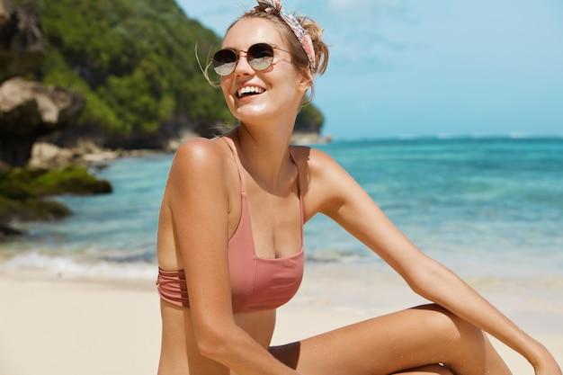 Ładna kobieta z okulary i strój kąpielowy na plaży