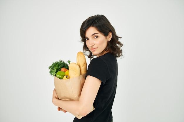 Ładna kobieta z opakowaniem żywności zdrowej żywności warzywa jasnym tle