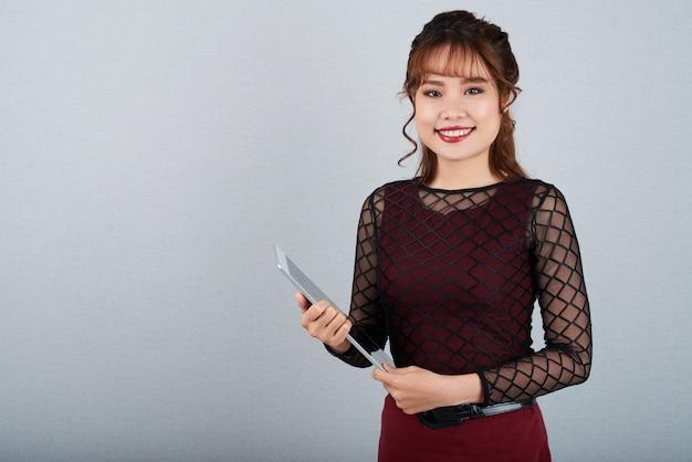 Ładna kobieta z pastylki komputerem ono uśmiecha się przy kamerą przeciw szarość