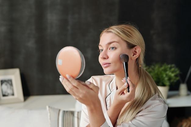 Ładna kobieta z pędzlem nakładającym puder na twarz i patrząc w lustro podczas robienia naturalnego makijażu
