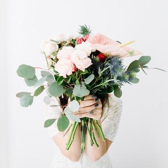 Ładna kobieta z pięknym bukietem kwiatów: bombastyczne róże, niebieskie eringium, kwiat anturium, gałęzie eukaliptusa na białej ścianie