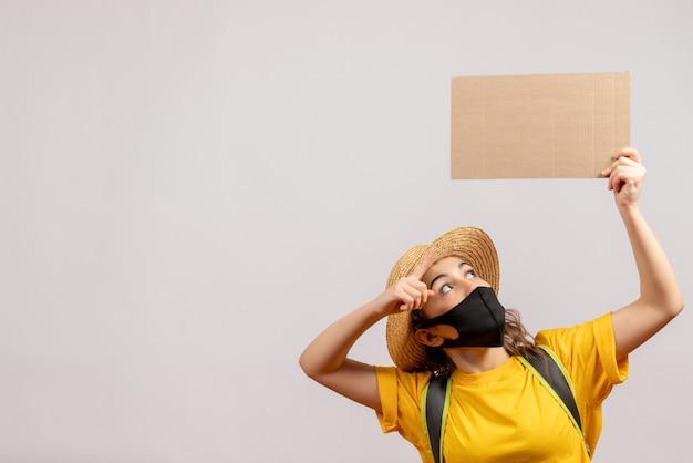 Ładna kobieta z plecakiem w czarnej masce trzymająca karton na białym cardboard