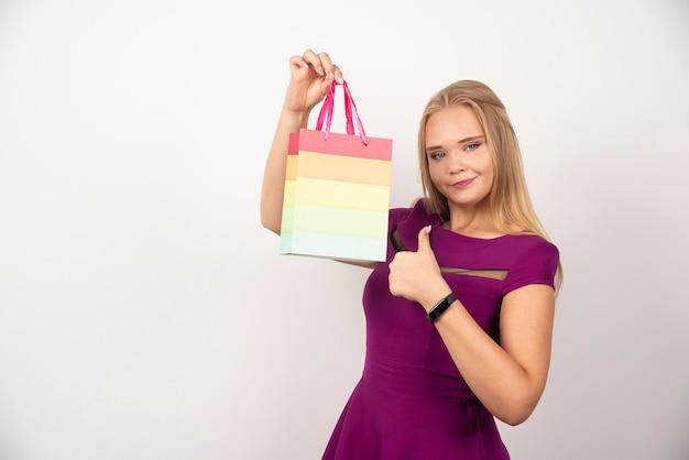 Ładna kobieta z prezentem torbą pozuje i pokazuje aprobaty.