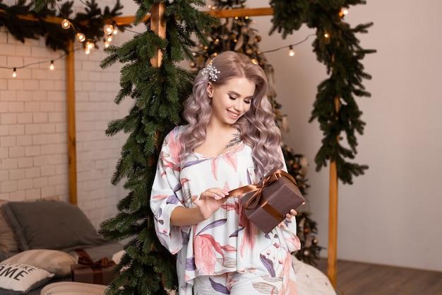 Ładna kobieta z pudełkiem prezentowym w ciepłych, przytulnych ubraniach w domu w pobliżu choinki