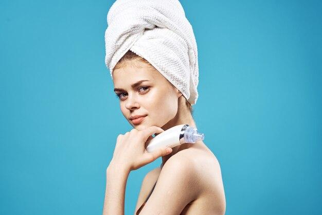 Ładna kobieta z ręcznikiem na głowie masuje pielęgnację skóry twarzy
