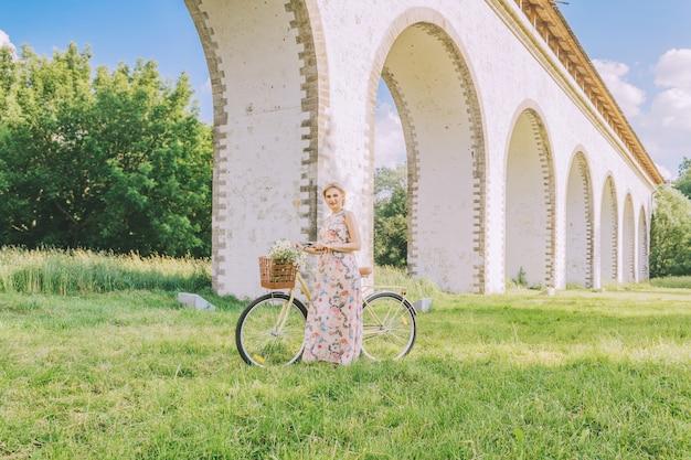 Ładna kobieta z rowerem na tle akweduktu mostu w sezonie letnim