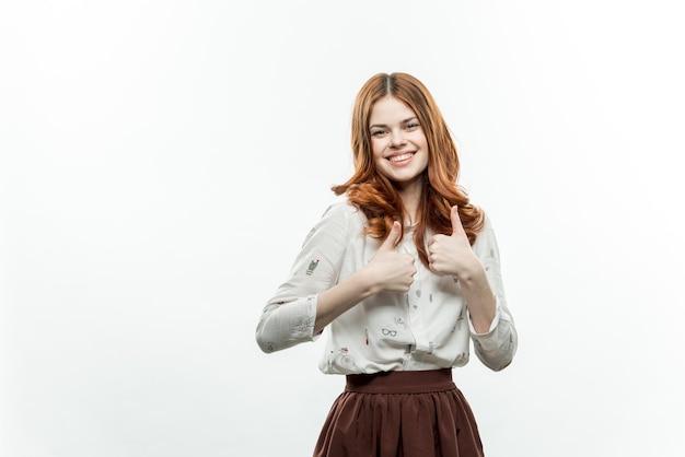 Ładna kobieta z rudymi włosami w garniturze gestykuluje z rękami uśmiech studio. wysokiej jakości zdjęcie