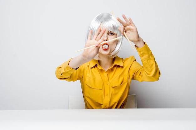 Ładna kobieta z siwymi włosami siedzi przy stole studio diety pałeczki do jedzenia.