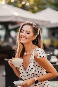 Ładna kobieta z szczerym uśmiechem, śmiejąc się, siedząc w letniej kawiarni przy filiżance cappuccino