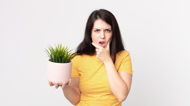 Ładna kobieta z szeroko otwartymi ustami i oczami, dłonią na brodzie i trzyma ozdobną roślinę
