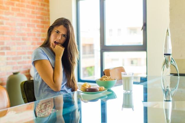 Ładna kobieta z szeroko otwartymi ustami i oczami i dłonią na brodzie, czująca się nieprzyjemnie zszokowana, mówiąca co lub wow