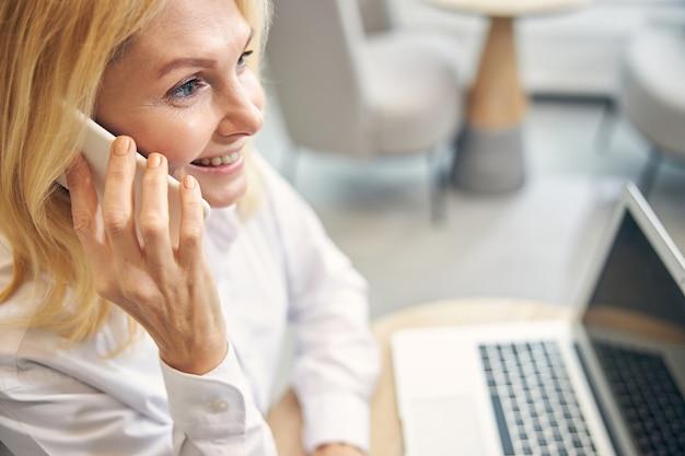 Ładna kobieta z uśmiechem na twarzy, siedząc przed laptopem w półpozycji