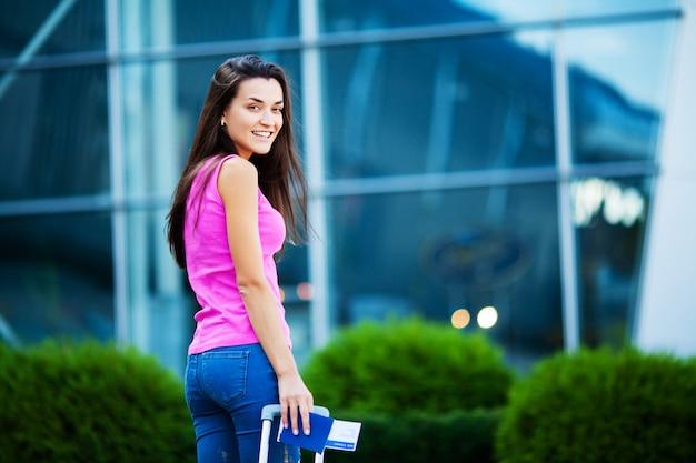 Ładna kobieta z walizką w pobliżu lotniska na wycieczkę