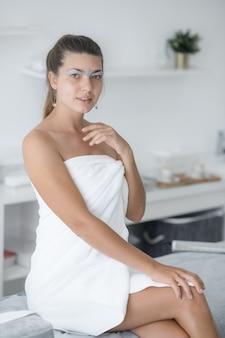Ładna kobieta z woskiem na brwiach w białym ręczniku