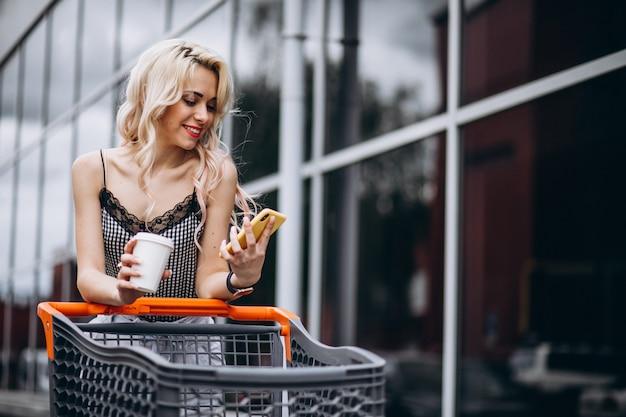 Ładna kobieta z wózek na zakupy outside