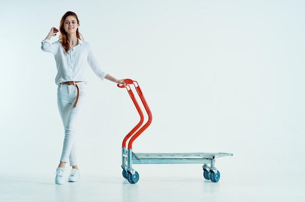 Ładna kobieta z wózkiem na zakupy w supermarkecie wysyłka