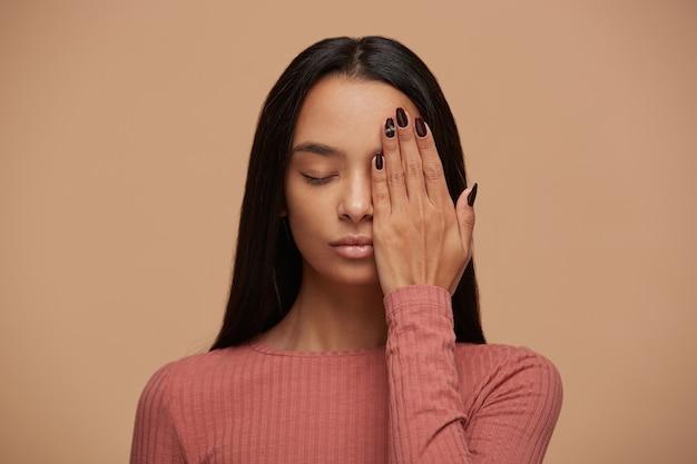 Ładna kobieta z zamkniętymi oczami chowa dłonią połowę twarzy, pokazuje piękny manicure