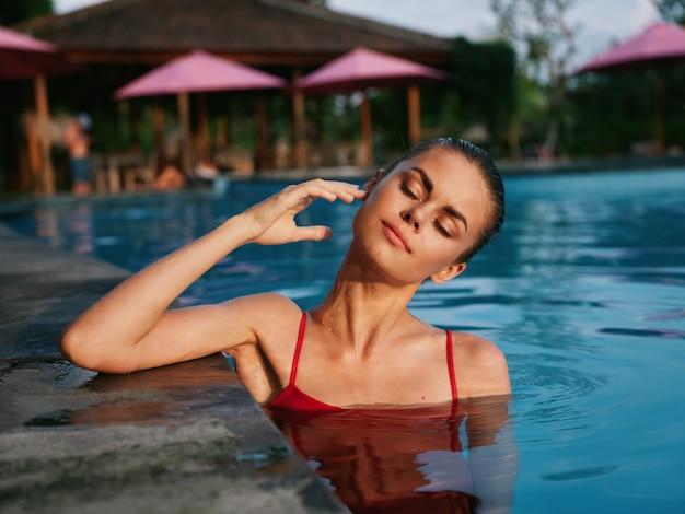 Ładna kobieta z zamkniętymi oczami w stroju kąpielowym w hotelowym basenie