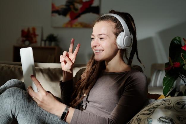 Ładna kobieta z zębatym uśmiechem pokazująca przyjacielowi gest pokoju na ekranie touchpada podczas rozmowy przez czat wideo