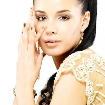 Ładna kobieta z złote paznokcie i piękną złotą biżuterię na białym tle
