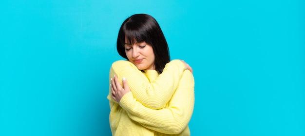 Ładna kobieta zakochana, uśmiechnięta, przytulająca się i przytulająca, pozostająca samotna, egoistyczna i egocentryczna