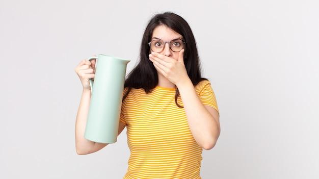 Ładna kobieta zakrywająca usta dłońmi zszokowanym i trzymająca termos z kawą