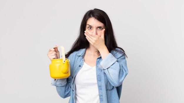 Ładna kobieta zakrywająca usta rękami zszokowana i trzymająca czajniczek