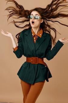 Ładna kobieta zaskoczona wyglądem w nowoczesnym stylu potargane włosy beżowe tło