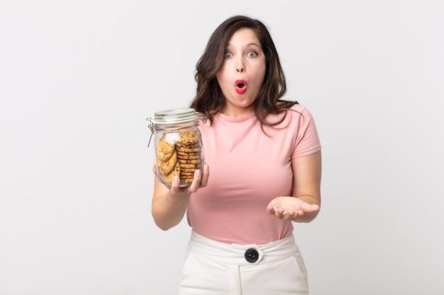 Ładna kobieta zdumiona, zszokowana i zdumiona niesamowitą niespodzianką, trzymająca szklaną butelkę po ciastkach