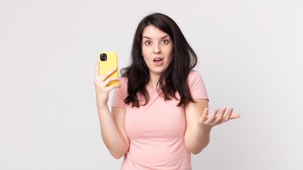 Ładna kobieta zdumiona, zszokowana i zdumiona niewiarygodną niespodzianką korzystającą ze smartfona