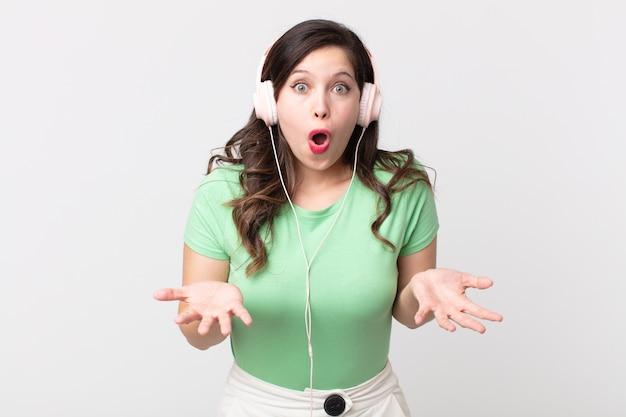 Ładna kobieta zdumiona, zszokowana i zdumiona niewiarygodnym zaskoczeniem słuchając muzyki przez słuchawki