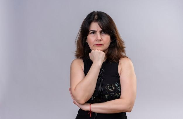 Ładna kobieta ze złością na sobie czarną bluzkę